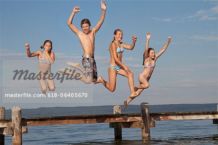 Young friends jumping from pier into sea Stock Photo - Premium Royalty-Free, Image code: 618-06405670