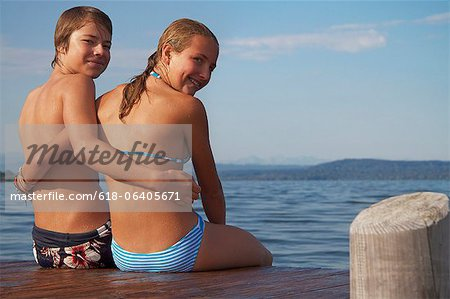 Young teenage couple sitting on pier, smiling, portrait Stock Photo - Premium Royalty-Free, Image code: 618-06405671