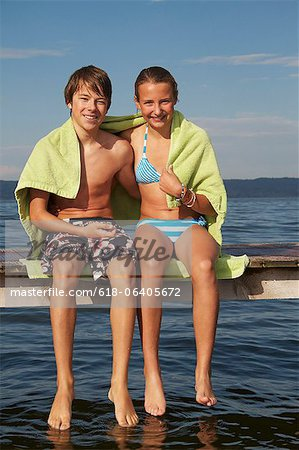 Young teenage couple sitting on pier, smiling, portrait Stock Photo - Premium Royalty-Free, Image code: 618-06405672