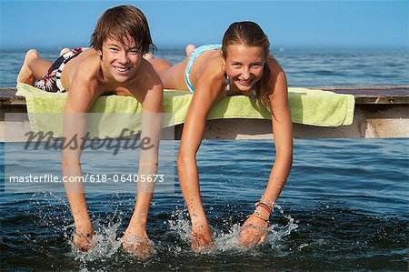 Young teenage couple lying on pier, smiling, portrait Stock Photo - Premium Royalty-Free, Image code: 618-06405673