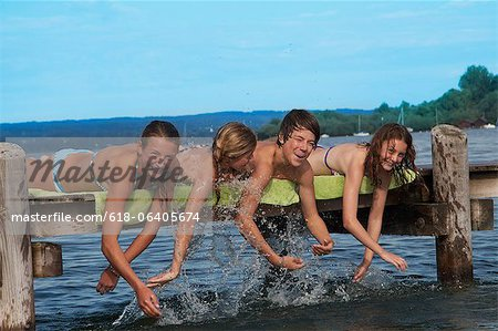 Four young friends splashing sweater from pier Stock Photo - Premium Royalty-Free, Image code: 618-06405674