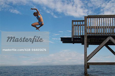 Young girl jumping into sea into pier Stock Photo - Premium Royalty-Free, Image code: 618-06405676