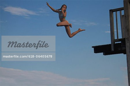 Young girl jumping into sea into pier Stock Photo - Premium Royalty-Free, Image code: 618-06405678