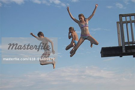 Young friends jumping into sea from pier Stock Photo - Premium Royalty-Free, Image code: 618-06405679