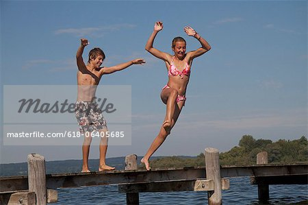 Young friends jumping into water from pier Stock Photo - Premium Royalty-Free, Image code: 618-06405685