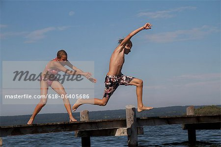 Young friends jumping into water from pier Stock Photo - Premium Royalty-Free, Image code: 618-06405686