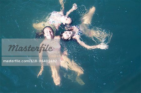 Young friends floating together in sea, high angle view Stock Photo - Premium Royalty-Free, Image code: 618-06405692