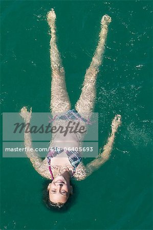 Girl floating in sea, high angle view Stock Photo - Premium Royalty-Free, Image code: 618-06405693