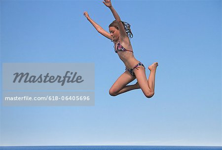 Girl jumping into sea, side view Stock Photo - Premium Royalty-Free, Image code: 618-06405696