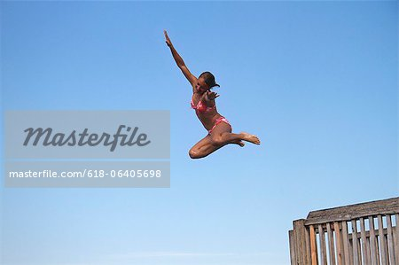 Girl jumping into sea, side view Stock Photo - Premium Royalty-Free, Image code: 618-06405698
