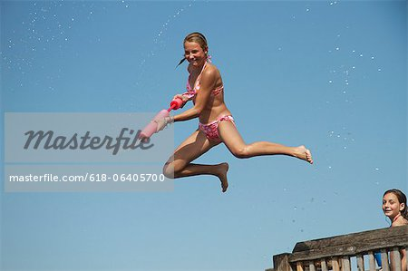 Girl jumping into sea holding water pistol, side view Stock Photo - Premium Royalty-Free, Image code: 618-06405700