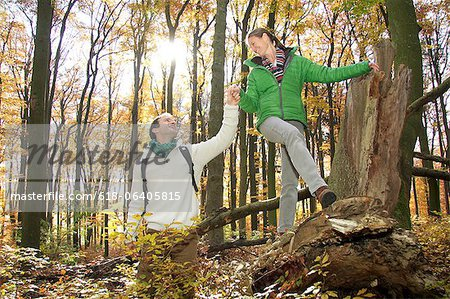 Mid adult man holding hand of woman climbing over log in forest