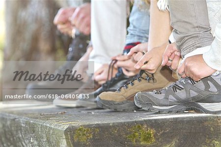 Family tying laces of hiking boots, close up Stock Photo - Premium Royalty-Free, Image code: 618-06405833