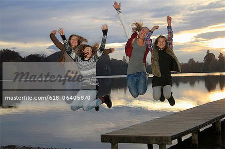 Girls jumping together on lake pier Stock Photo - Premium Royalty-Free, Image code: 618-06405870