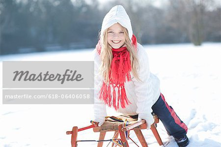 Young girl leaning on sledge, smiling, portrait Stock Photo - Premium Royalty-Free, Image code: 618-06406058