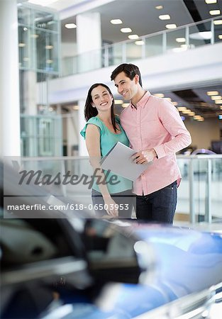 Smiling couple looking at car in car dealership showroom Stock Photo - Premium Royalty-Free, Image code: 618-06503953
