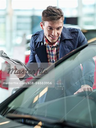 Smiling man with brochure looking at car in car dealership showroom Stock Photo - Premium Royalty-Free, Image code: 618-06503956
