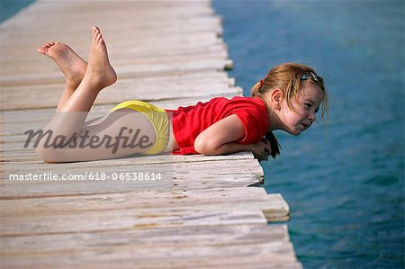young girl lying on wooden pier Stock Photo - Premium Royalty-Free, Image code: 618-06538614
