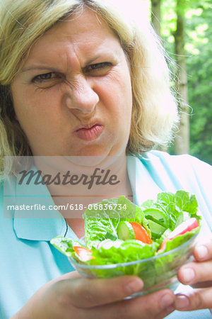 Mature woman grimacing at salad, outdoors Stock Photo - Premium Royalty-Free, Image code: 618-06836734