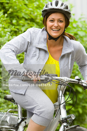 Portrait of young woman sitting on bicycle, smiling Stock Photo - Premium Royalty-Free, Image code: 618-06836737