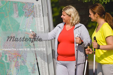Two friends holding hiking poles and looking at map Stock Photo - Premium Royalty-Free, Image code: 618-06836738