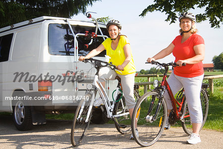 Two friends sitting on bicycles, portrait Stock Photo - Premium Royalty-Free, Image code: 618-06836740