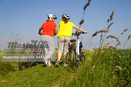 Two friends walking with bicycles through field Stock Photo - Premium Royalty-Free, Image code: 618-06836742