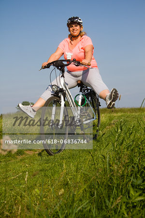 Mature woman cycling through field, smiling Stock Photo - Premium Royalty-Free, Image code: 618-06836744