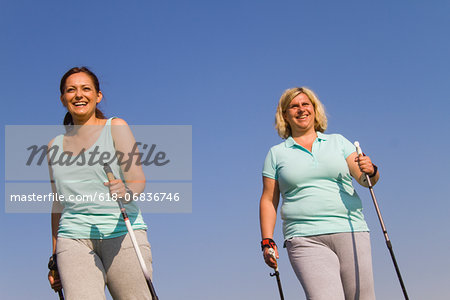 Two friends hiking against blue sky Stock Photo - Premium Royalty-Free, Image code: 618-06836746