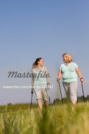 Two friends hiking through field, smiling Stock Photo - Premium Royalty-Free, Image code: 618-06836747