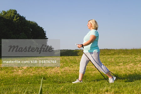 Mature woman hiking through field Stock Photo - Premium Royalty-Free, Image code: 618-06836748