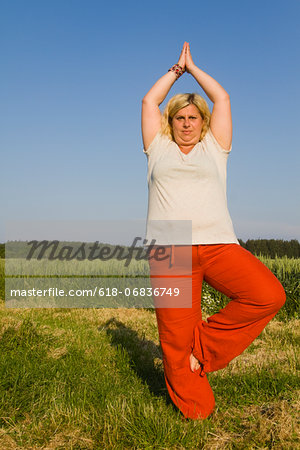 Mature woman performing tree pose in field Stock Photo - Premium Royalty-Free, Image code: 618-06836749