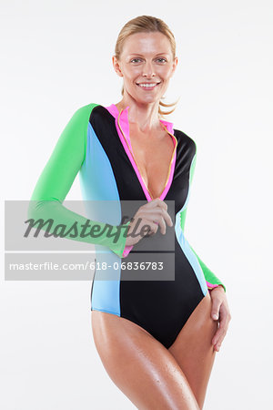 Portrait of mid adult woman unzipping swimsuit against white background Stock Photo - Premium Royalty-Free, Image code: 618-06836783