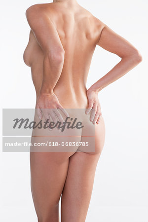 Naked mid adult woman standing in studio against white background Stock Photo - Premium Royalty-Free, Image code: 618-06836785