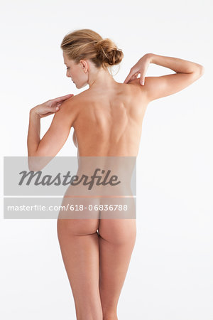 Naked mid adult woman standing in studio against white background Stock Photo - Premium Royalty-Free, Image code: 618-06836788