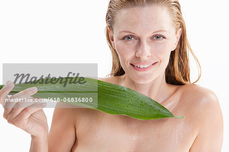 Portrait of mid adult woman holding leaf, studio shot Stock Photo - Premium Royalty-Free, Image code: 618-06836800