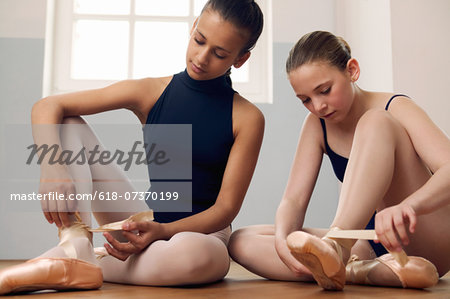 Two female ballet dancers (11-13) on floor, tying up shoes Stock Photo - Premium Royalty-Free, Image code: 618-07370199