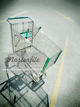 Vignette of empty shopping cart in parking lot Stock Photo - Premium Royalty-Free, Image code: 618-07385028