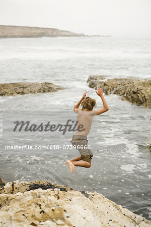 kid jumping into the ocean Stock Photo - Premium Royalty-Free, Image code: 618-07396666