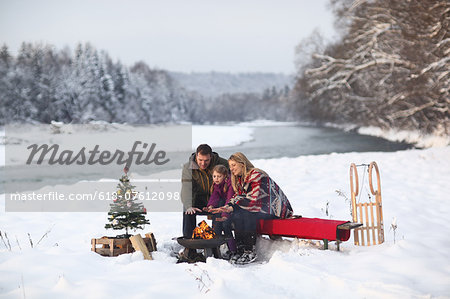 Family sitting at campfire in snow Stock Photo - Premium Royalty-Free, Image code: 618-07612098