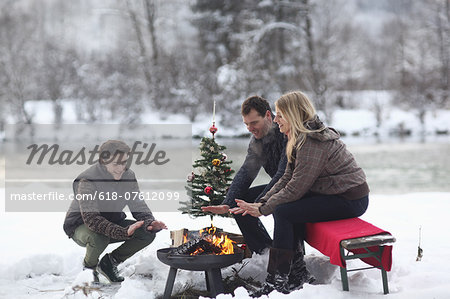 Family sitting at campfire in snow Stock Photo - Premium Royalty-Free, Image code: 618-07612099