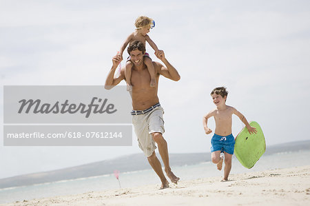 Father and boys running on beach Stock Photo - Premium Royalty-Free, Image code: 618-07612144