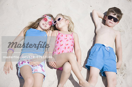 Boy and girls lying together on beach Stock Photo - Premium Royalty-Free, Image code: 618-07612146