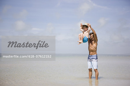 Father lifting boy above sea Stock Photo - Premium Royalty-Free, Image code: 618-07612152