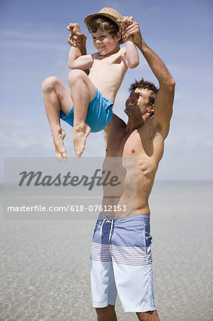 Father lifting boy above sea Stock Photo - Premium Royalty-Free, Image code: 618-07612153