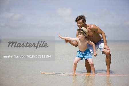father teaching son how to surf in sea Stock Photo - Premium Royalty-Free, Image code: 618-07612154