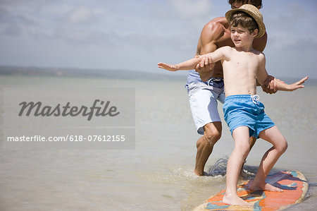 father teaching son how to surf in sea Stock Photo - Premium Royalty-Free, Image code: 618-07612155