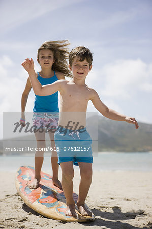 Boy and girl balancing on surfboard on beach Stock Photo - Premium Royalty-Free, Image code: 618-07612157