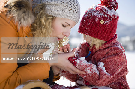 Mother blowing snow from daughters hands Stock Photo - Premium Royalty-Free, Image code: 618-07612297