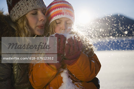 Mother and girl blowing snow Stock Photo - Premium Royalty-Free, Image code: 618-07612302